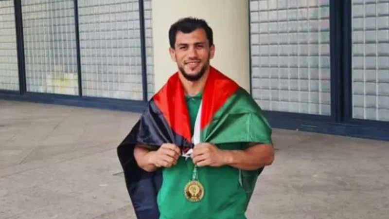 The Palestinian flag is draped around the shoulders of a smiling man
