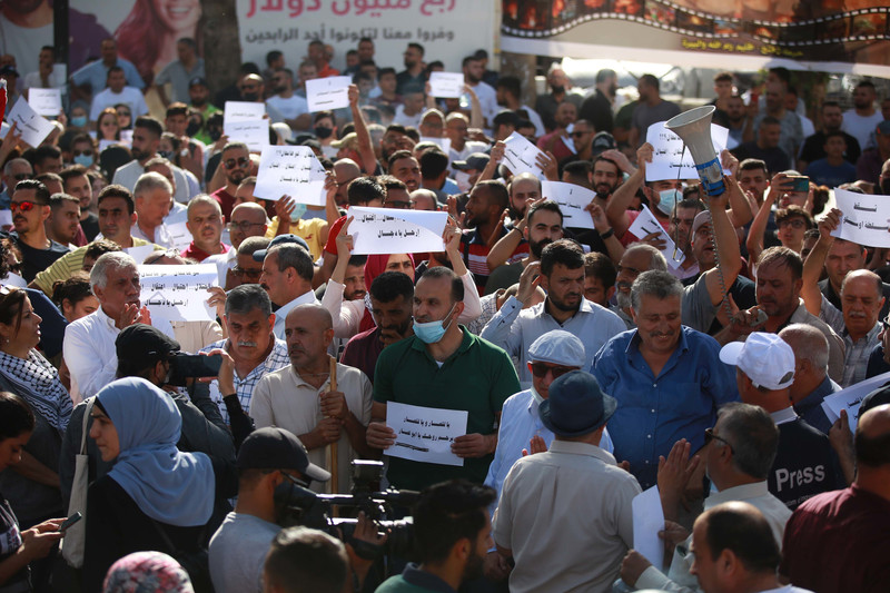 Demonstrators hold up signs in Arabic