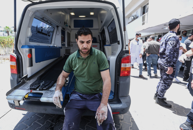 A man rests by the open back of an ambulance