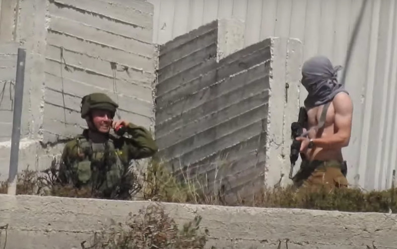 Smiling man in military uniform gestures towards man with shirt pulled over his head carrying rifle