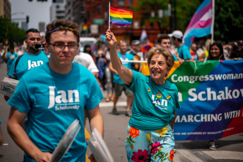 Woman waves rainbow flag as people march