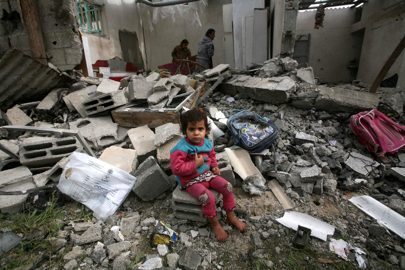 A young child sits in rubble