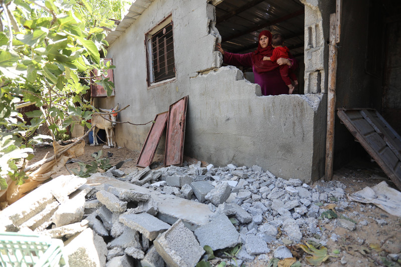 A woman stands behind the remains of a wall of her home