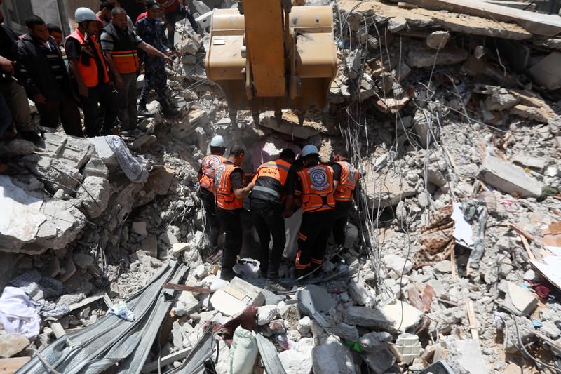 Men in florescent vests stand next to excavator machine atop rubble