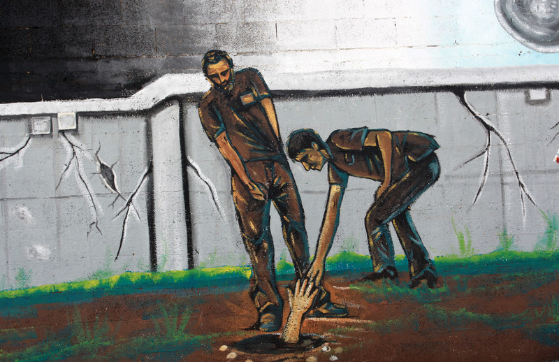 A mural depicts two men reaching out for a hand in a hole in the ground