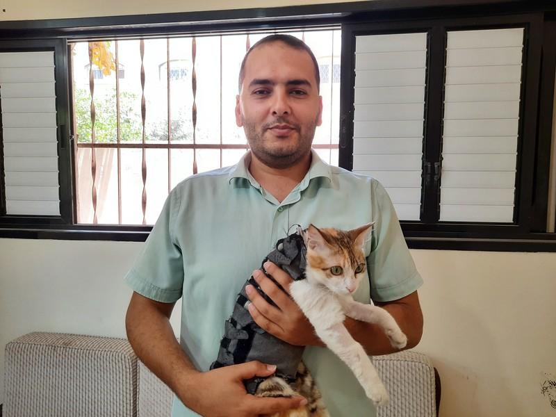 A man holds a cat wearing a black vest