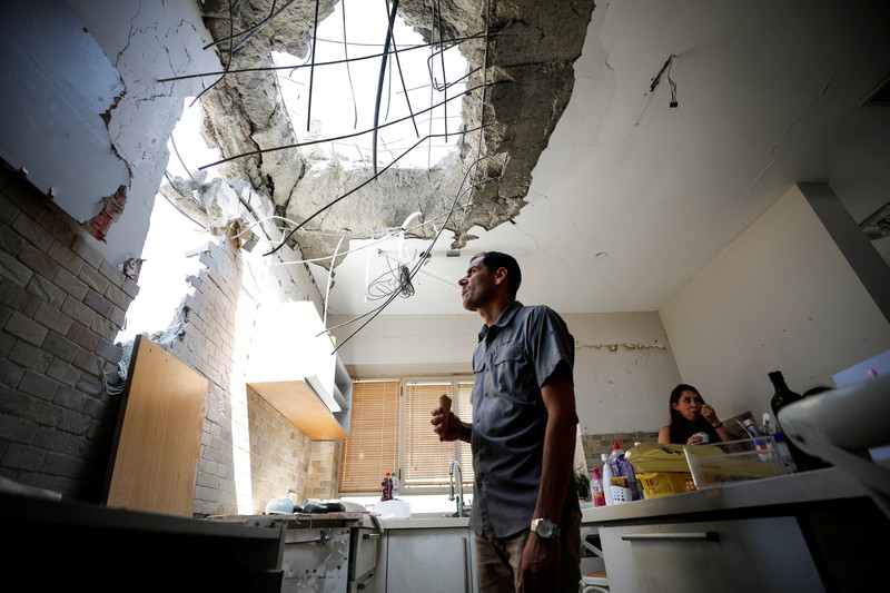 Man stands underneath hole in kitchen ceiling