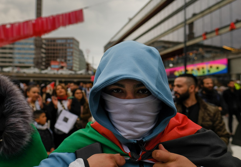 Close up of man in face mask and hoodie carrying Palestinian flag