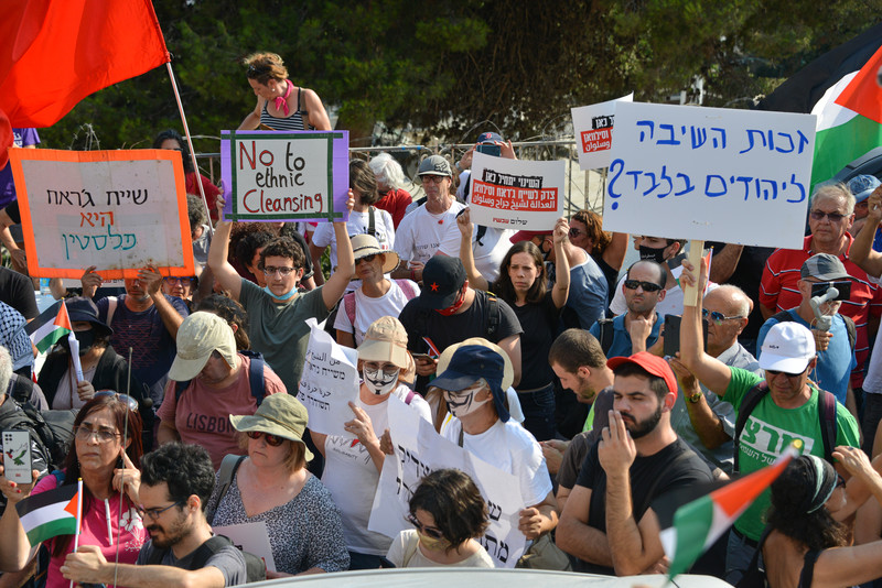 A crowd of protestors hold up the Palestinian flag and signs in Arabic, Hebrew and English