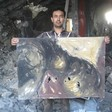 Artist Raed Issa holds up one of his damaged paintings in his bombed-out house in Gaza