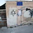 Woman stands behind bars next to walls spray-painted with Stars of David