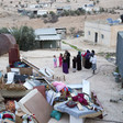 Women and children stand near home with possessions piled up outside