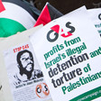 Protest signs read: G4S profits from Israel's illegal detention and torture of Palestinians