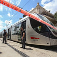 Two guards stand in front of light rail train surrounded by red tape