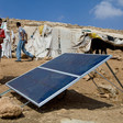 A boy stands next to a solar panel installed on barren ground with makeshift shelters in the background