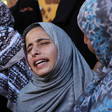 Girl wearing head scarf, seen from shoulders up, is comforted by woman while she cries