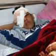 Boy with bandaged head and eye lies on a bed, covered with a blanket