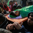 Shrouded body of boy is carried on a stretcher during funeral procession