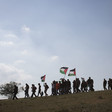 Protestors wave Palestinian flags in an open land