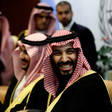 Saudi crown prince is seen smiling from chest up while wearing robe and checkered headdress