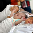 Photo shows three swaddled newborns lying on their backs