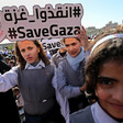 Girls in school uniform hold sign reading #SaveGaza in English and Arabic