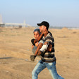 A man carries a boy with a bandaged leg across a sandy landscape