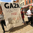 Activists hold large banner reading Gaza How Much More? with image of burning buildings on it