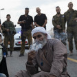 Palestinians sit near Israeli police during an early morning raid.