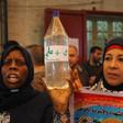 "Palestinian women holding up a bottlereading ""waterandsalt."""