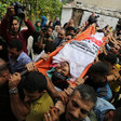 The body of a young man wrapped in a faction flag is carried on a stretcher by a crowd