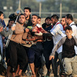 Around a dozen men carry a man who is bleeding from the neck with the Gaza boundary fence in the background