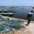 A young man pulls on a pile of fishing nets while standing next to docked boats