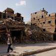 Man walks down street with ruins of multi-story buildings behind him