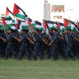 Young men wearing camouflage uniforms and berets carry Palestine flags while marching during graduation ceremony