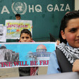 Children standing in front of UNRWA headquarters in Gaza hold signs saying Palestine Will be Free and Jerusalem is Our Land