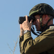 A man in military uniform looks through binoculars