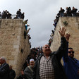 A man raising his hand surrounded by crowds with Bab al-Rahma gate in the background.