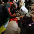 Men and women crowd around body shrouded in Palestine flag