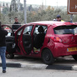 Men stand around car behind police tape