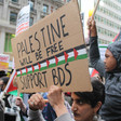 A protester holds a sign that says Palestine will be free, support BDS.