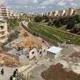 Hyundai bulldozers demolish home amid buildings and fields.