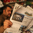A man reads an Arabic-language newspaper in a shop