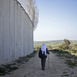Palestinian man using a cane walks along dirt path next to concrete wall and barbed wire