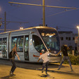 Youths throw stones at a tram