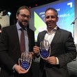 """Two men smile and hold trophies that say """"Horizon 2020"""""""