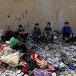 Six boys surrounded by rubble and damaged belongings
