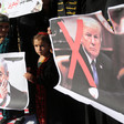 Girls hold signs with faces of Donald Trump and Benjamin Netanyahu crossed out.