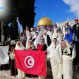 People hold the Tunisian flag near the Dome of the Rock.