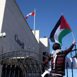A protester waves a Palestinian flag over the gate of the Canadian mission in Ramallah.